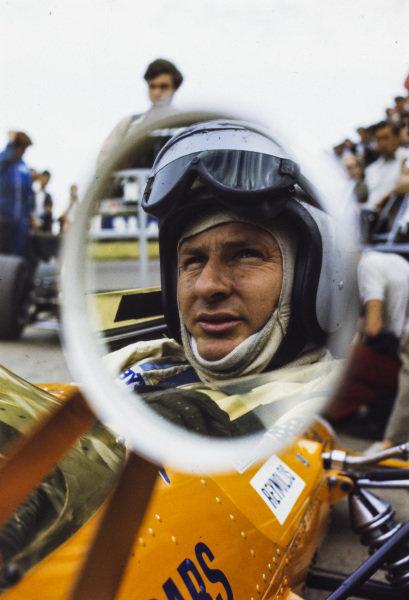 Bruce McLaren reflected in the mirror of his McLaren M7C Ford.