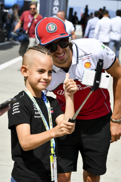 Antonio Giovinazzi, Alfa Romeo Racing poses for a photograph with a young fan in the paddock