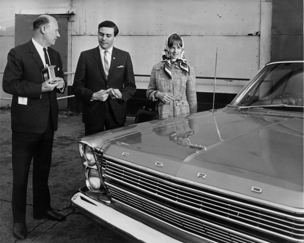 Jim Clark picks up the keys to a brand new-right-hand drive, Ford Galaxie with girlfriend, Sally Stokes, after winning the Indianapolis 500, portrait. World Copyright: LAT Photographic.Ref:  B/W PRINT.
