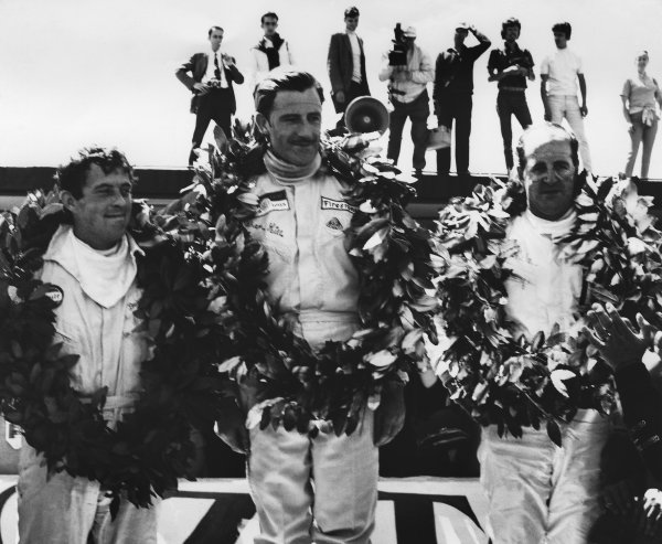 1968 Spanish Grand Prix. Jarama, Spain. 12 May 1968. Rd 2. Graham Hill (Lotus 49-Ford), 1st position, with Denny Hulme (McLaren M7A-Ford), 2nd position and Brian Redman (Cooper T86B-BRM), 3rd position, on the podium, portrait. World Copyright: LAT Photographic. Ref: B/W Print.