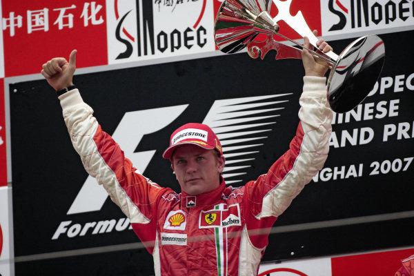Kimi Räikkönen raises his winner's trophy on the podium.