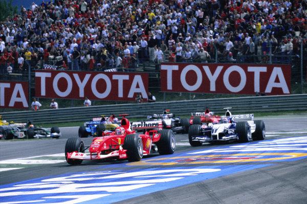 Michael Schumacher, Ferrari F2003-GA, leads Juan Pablo Montoya, Williams FW25 BMW, Rubens Barrichello, Ferrari F2003-GA, and Kimi Räikkönen, McLaren MP4-17D Mercedes, round the first corner.