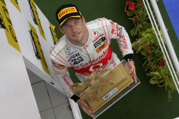Jenson Button, 1st position, on the podium with his trophy.