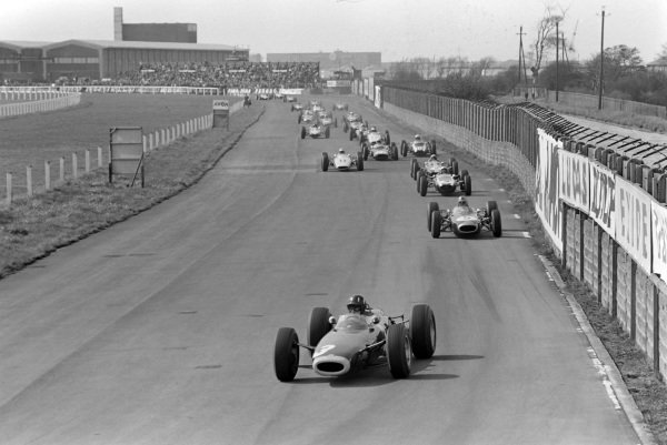 Graham Hill, BRM P261, leads Bruce McLaren, Cooper T73 Climax, Jack Brabham, Brabham BT7 Climax, Peter Arundell, Lotus 25 Climax, Innes Ireland, BRP 2 BRM, Jo Bonnier, Cooper T66 Climax, Phil Hill, Cooper T66 Climax, Trevor Taylor, BRP 1 BRM, and Jim Clark, Lotus 33 Climax, on the opening lap.