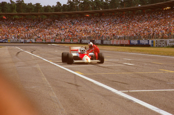 Hockenheim, Germany.25-27 July 1986.Alain Prost (McLaren MP4/2C TAG Porsche) ran out of fuel on the last lap and dropped from 3rd to 6th position, as he pushes his car across the finish line.Ref-86 GER 12.World Copyright - LAT Photographic