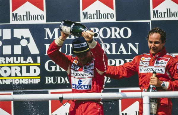 Ayrton Senna and Gerhard Berger, celebrate on the podium.