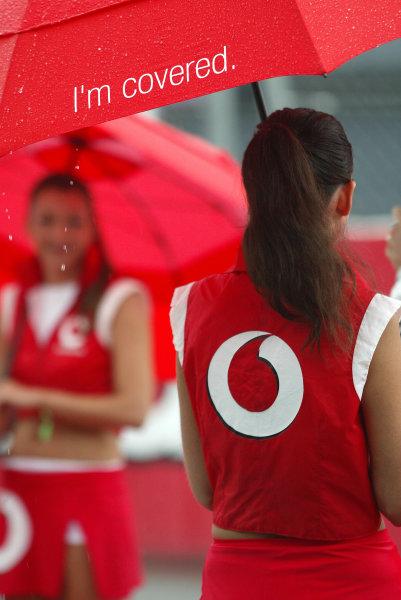2004 Italian Grand Prix - Sunday Race,Monza, Italy. 12th September 2004 Grid girls shelter from the rain.World Copyright: Steve Etherington/LAT Photographic ref: Digital Image Only