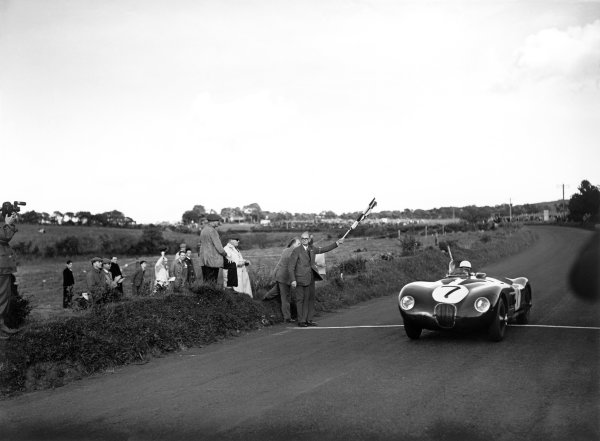 Dundrod, Northern Ireland. 15th August 1951. Stirling Moss (C-Type Jaguar), 1st position, takes the chequered flag, action. World Copyright: LAT Photographic. Ref: Autocar Glass Plate C30336.