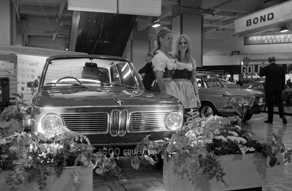 Two models in Bavarian dress pose beside a BMW 1600.