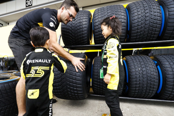 Young fans check out the Pirelli tyres of the Reanult team.