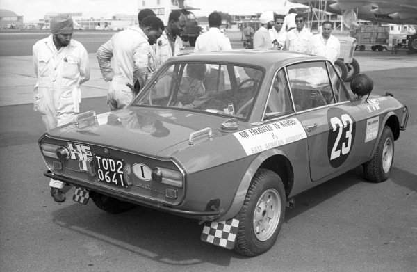 """Sandro Munari and """"Lofty"""" Drews Lancia Fulvia coupe is perused by ground engineers after being aifreighted to Kenya."""