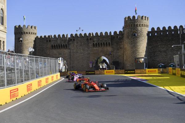 Carlos Sainz Jr., McLaren MCL34, leads Lance Stroll, Racing Point RP19, and Alexander Albon, Toro Rosso STR14
