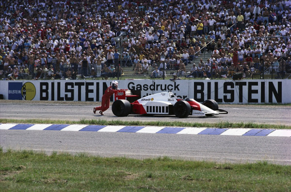 Alain Prost pushes his McLaren MP4-2C TAG after running out of fuel on the last lap.