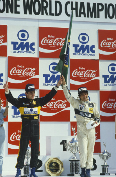 Jacarepagua, Rio de Janeiro, Brazil.21-23 March 1986.Nelson Piquet (Williams Honda) and Ayrton Senna (Team Lotus) celebrate home drivers finishing in 1st and 2nd positions.World Copyright: LAT Photographic.Ref:  Colour Transparency.