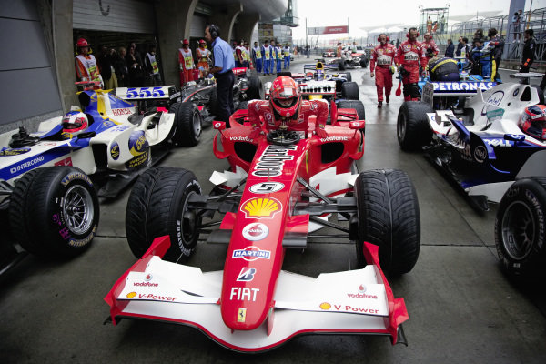 Michael Schumacher climbing out of his Ferrari 248 F1 in parc fermé after qualifying.