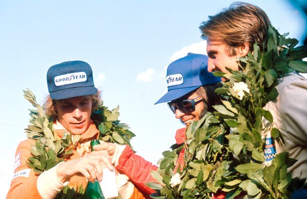 1975 Argentinian Grand Prix.Buenos Aires, Argentina.10-12 January 1975.Emerson Fittipaldi (McLaren Ford) 1st position, James Hunt (Hesketh Ford) 2nd position and Carlos Reutemann (Brabham Ford) 3rd position on the podium.Ref-75 ARG 07.World Copyright - LAT Photographic