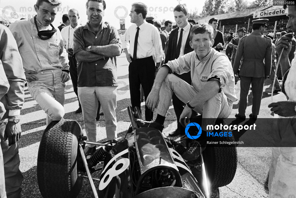 Jochen Rindt sits on his Cooper T73 Climax alongside Jo Siffert and John Cooper on the grid before the start.