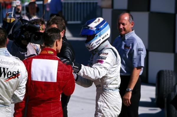 Michael Schumacher (GER) Ferrari, left, congratulates race winner Mika Hakkinen (FIN) McLaren. Ron Dennis (GBR) McLaren team manager, far right, looks on. United States Grand Prix, Indianapolis, 30 September 2001 BEST IMAGE