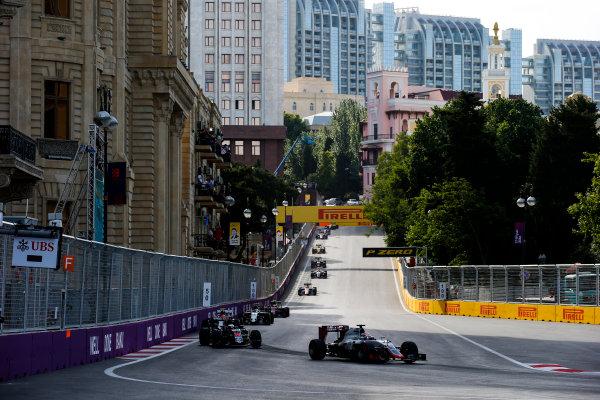 Baku City Circuit, Baku, Azerbaijan. Sunday 19 June 2016. Romain Grosjean, Haas VF-16. leads Fernando Alonso, McLaren MP4-31 Honda, at the start of the race World Copyright: Sam Bloxham/LAT Photographic ref: Digital Image _SLA3505