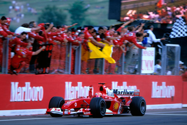 2004 Hungarian Grand Prix  Hungaroring, Hungary. 13th - 15th August.  Michael Schumacher, Ferrari F2004 crosses the line to take his twelfth victory of the year and sealed the constructors championship for Ferrari. Action.  World Copyright:Charles Coates/LAT Photographic  Ref:35mm Image:A16
