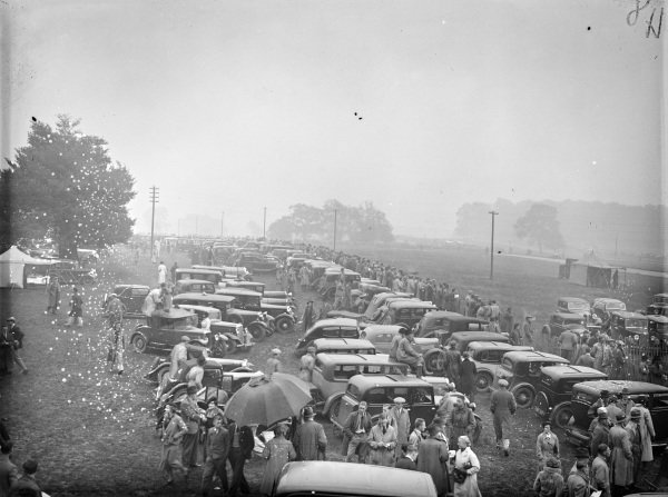 A large number of spectators' vehicles parked behind where fans gather to watch the action.