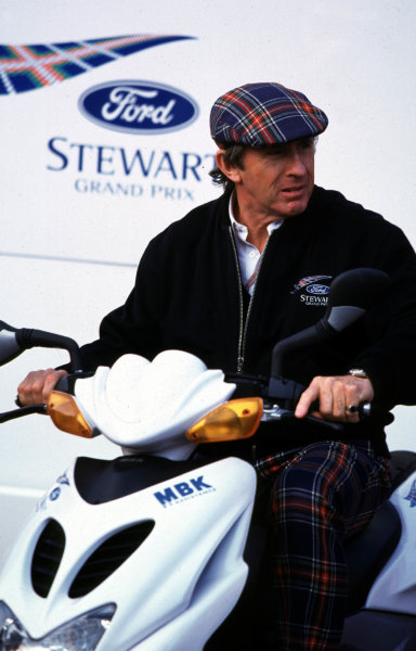 1998 Belgian Grand Prix.Spa-Francorchamps, Belgium. 28-30 August 1998.Jackie Stewart (Stewart Ford) on a scooter.World Copyright - LAT Photographic