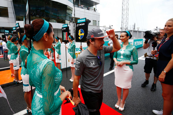 Sepang International Circuit, Sepang, Malaysia. Sunday 01 October 2017. Fernando Alonso, McLaren, walks through a corridor of grid girls. World Copyright: Andy Hone/LAT Images  ref: Digital Image _ONY4415