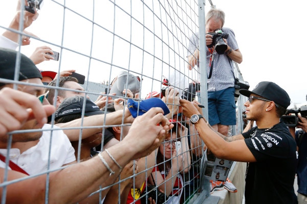 Circuit Gilles Villeneuve, Montreal, Canada. Sunday 7 June 2015. Lewis Hamilton, Mercedes AMG, 1st Position, celebrates with and signs autographs for fans. World Copyright: Alastair Staley/LAT Photographic. ref: Digital Image _79P5765