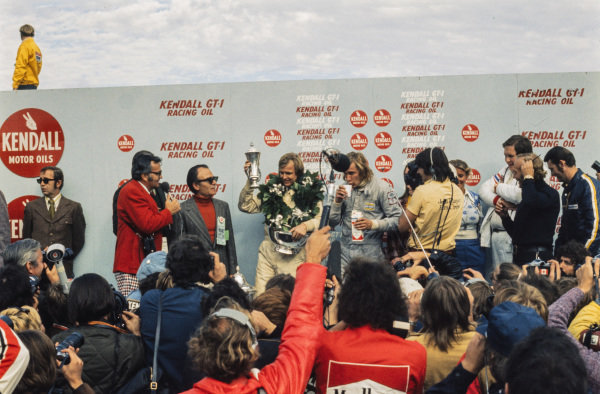 Ronnie Peterson celebrates victory on the podium with James Hunt, 2nd position, while their respective team bosses Colin Chapman and Lord Hesketh watch on. Peterson's wife, Barbro, is also on the podium.