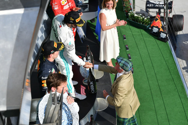 Lewis Hamilton, Mercedes AMG F1, 1st position, shakes hands with Sir Jackie Stewart, 3-time F1 Champion, on the podium