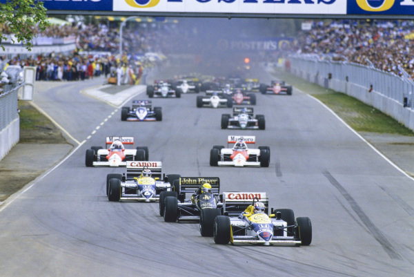 Nigel Mansell, Williams FW11 Honda, leads Ayrton Senna, Lotus 98T Renault, Nelson Piquet, Williams FW11 Honda, Alain Prost, McLaren MP4-2C TAG, and Keke Rosberg, McLaren MP4-2C TAG, at the start.