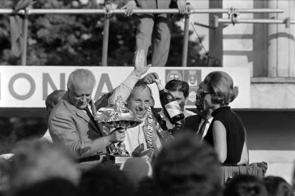 John Surtees, 1st position, is presented with his winner's trophy and champagne.