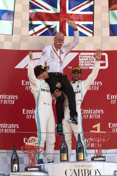 Valtteri Bottas, Mercedes AMG F1, 2nd position, and Lewis Hamilton, Mercedes AMG F1, 1st position, lifts Dr Dieter Zetsche, CEO, Mercedes Benz, onto their shoulders on the podium