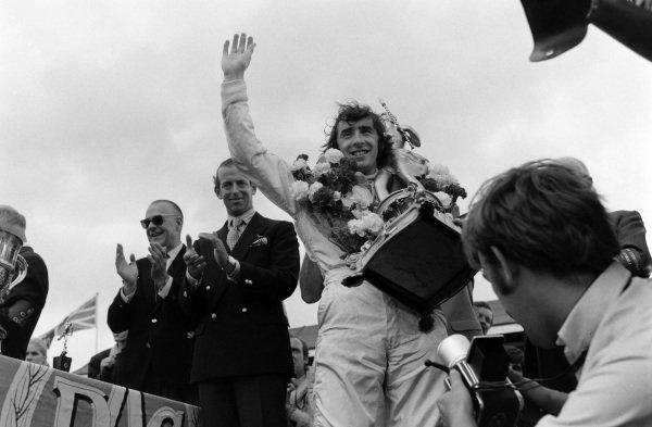 Race winner Jackie Stewart receives his trophy on the podium.
