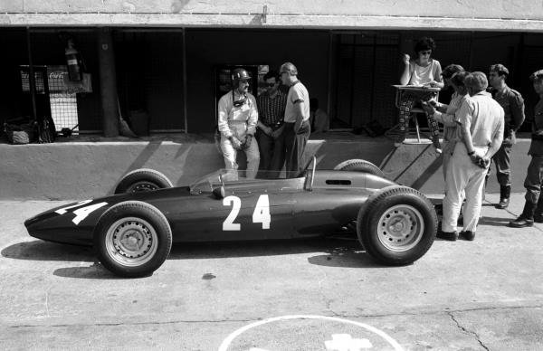 Graham Hill (GBR) and his BRM P48/57 wait for action in the pits. He talks with Lotus Team Owner Colin Chapman . HillÕs wife Bette monitors the lap times from the pit wall.