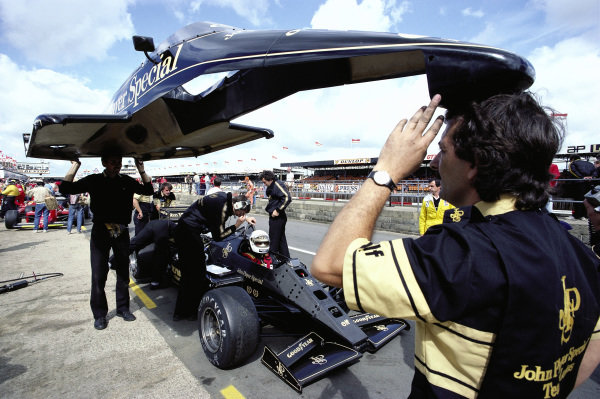 Mechanics lift bodywork over Elio de Angelis, Lotus 97T Renault, in the pits.