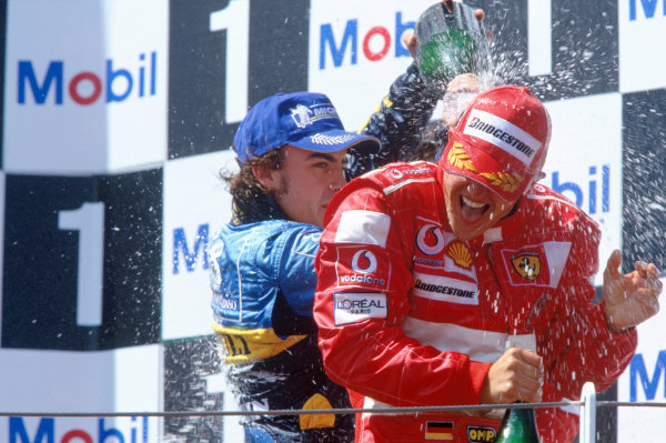 2004 French Grand PrixMagny-Cours, France. 2nd - 4th JulyMichael Schumacher, Ferrari F2004 and Fernando Alonso, Renault R24 celebrate on the podium.World Copyright: LAT PhotographicRef:35mm Image A06