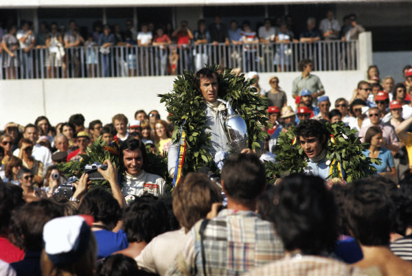 Jackie Stewart celebrates victory on the podium with team mate Francois Cevert, 2nd and Emerson Fittipaldi, 3rd.