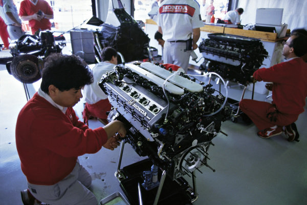 Honda mechanics work on engines in the McLaren garage.