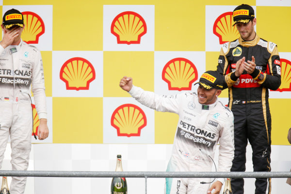 Spa-Francorchamps, Spa, Belgium. Sunday 23 August 2015. Lewis Hamilton, Mercedes AMG, 1st Position, Nico Rosberg, Mercedes AMG, 2nd Position, and Romain Grosjean, Lotus F1, 3rd Position, on the podium. World Copyright: Alastair Staley/LAT Photographic ref: Digital Image _79P5460