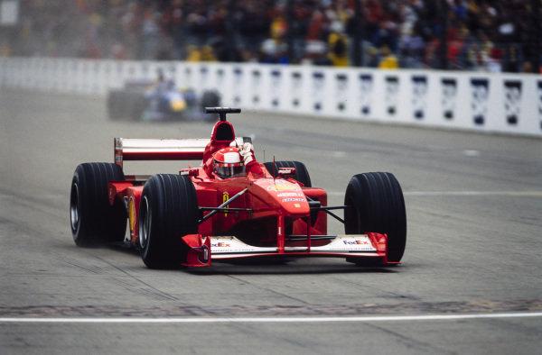Michael Schumacher, Ferrari F1-2000, celebrates as he crosses the line for victory.