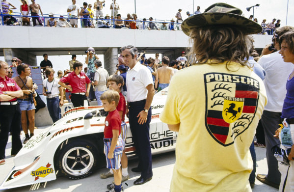 Roger Penske stands for a picture with two young spectators. A Porsche fan looks on.