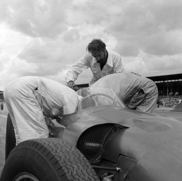 Mechanics work on a Aston Martin DBR5/250 in the pits.
