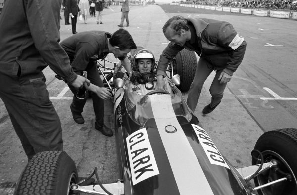 Jim Clark, Lotus 33 Climax, returns to the pit lane after claiming victory to be congratulated by mechanics and team boss Colin Chapman.