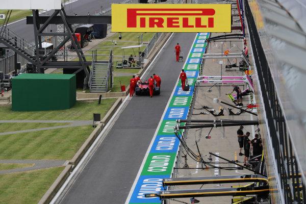 The Sebastian Vettel Ferrari SF1000 is pushed by mechanics in the pit lane